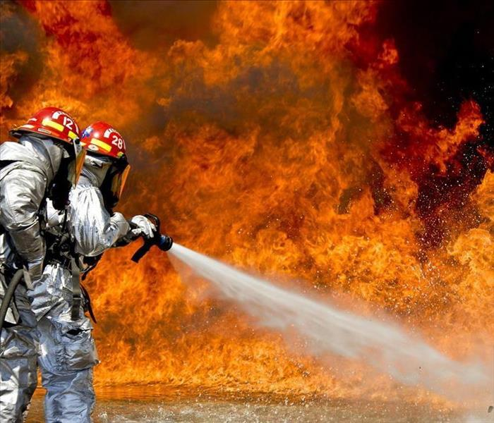 Image shows firemen putting out a fire